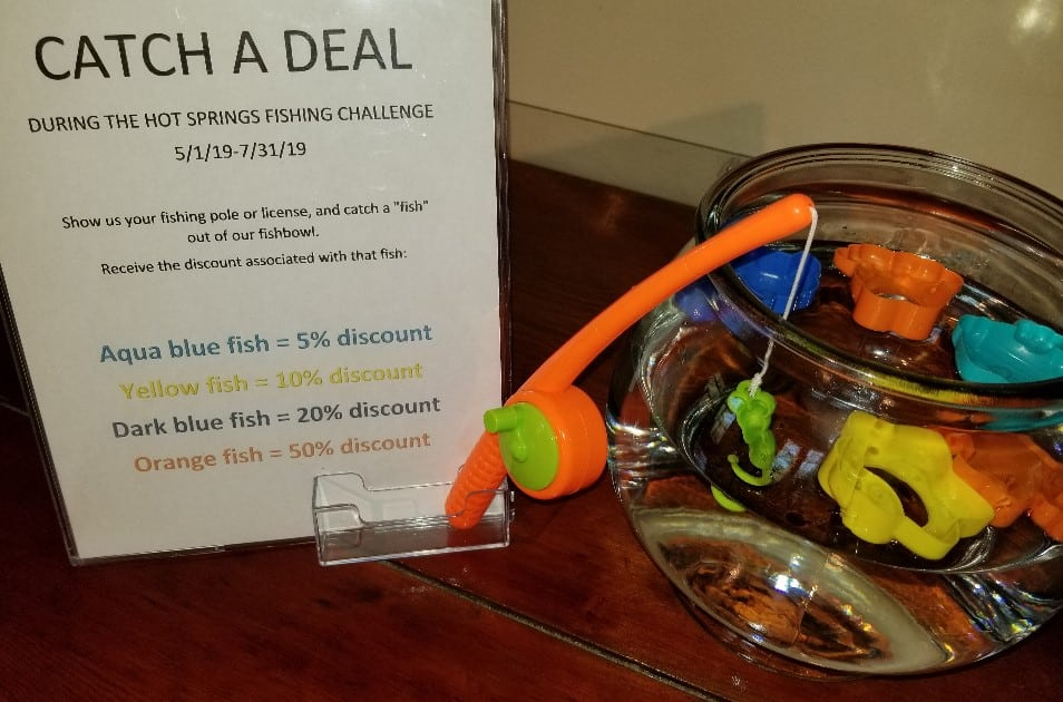 fish bowl with toy fish and fishing rod with a sign that reads Catch a Deal