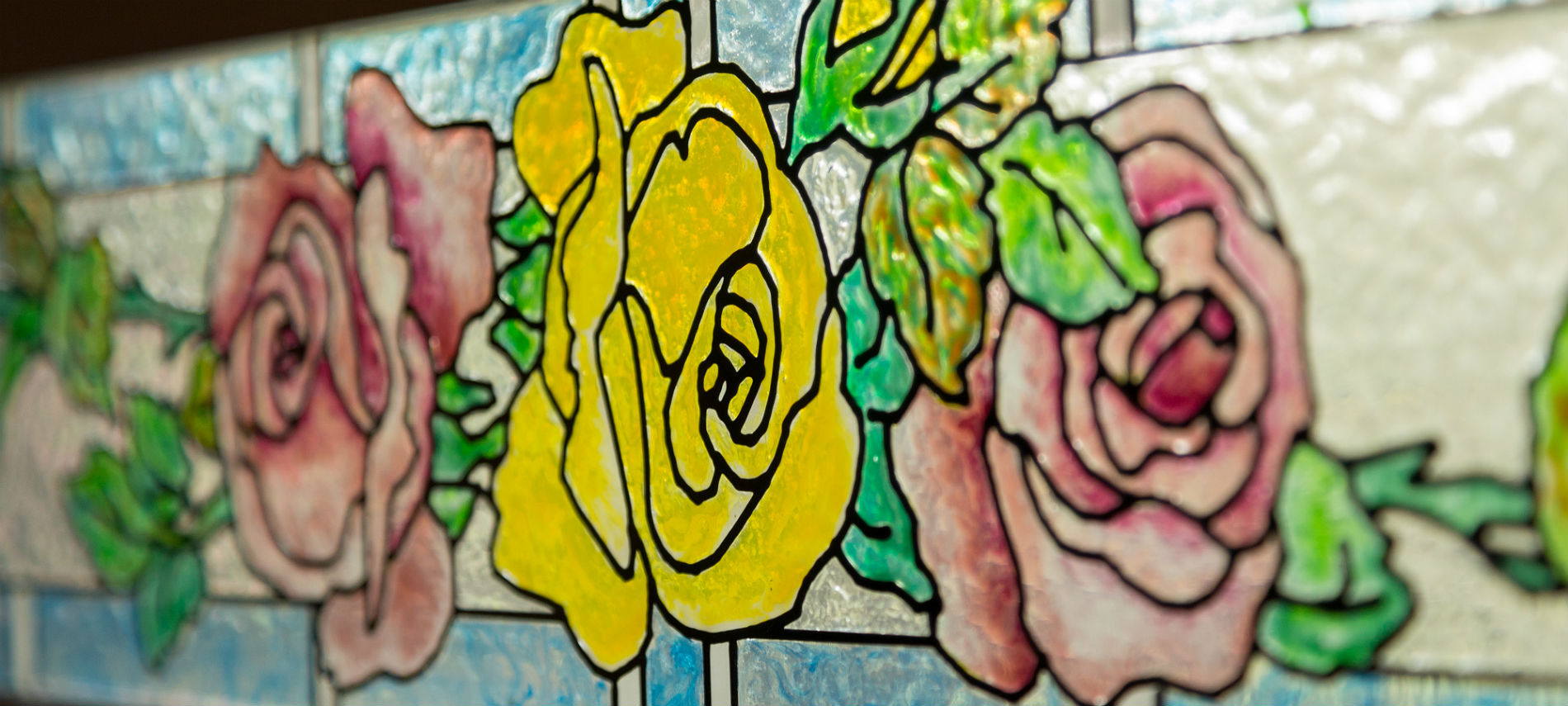 Close up of a stained glass window of pink and yellow roses and a blue border.