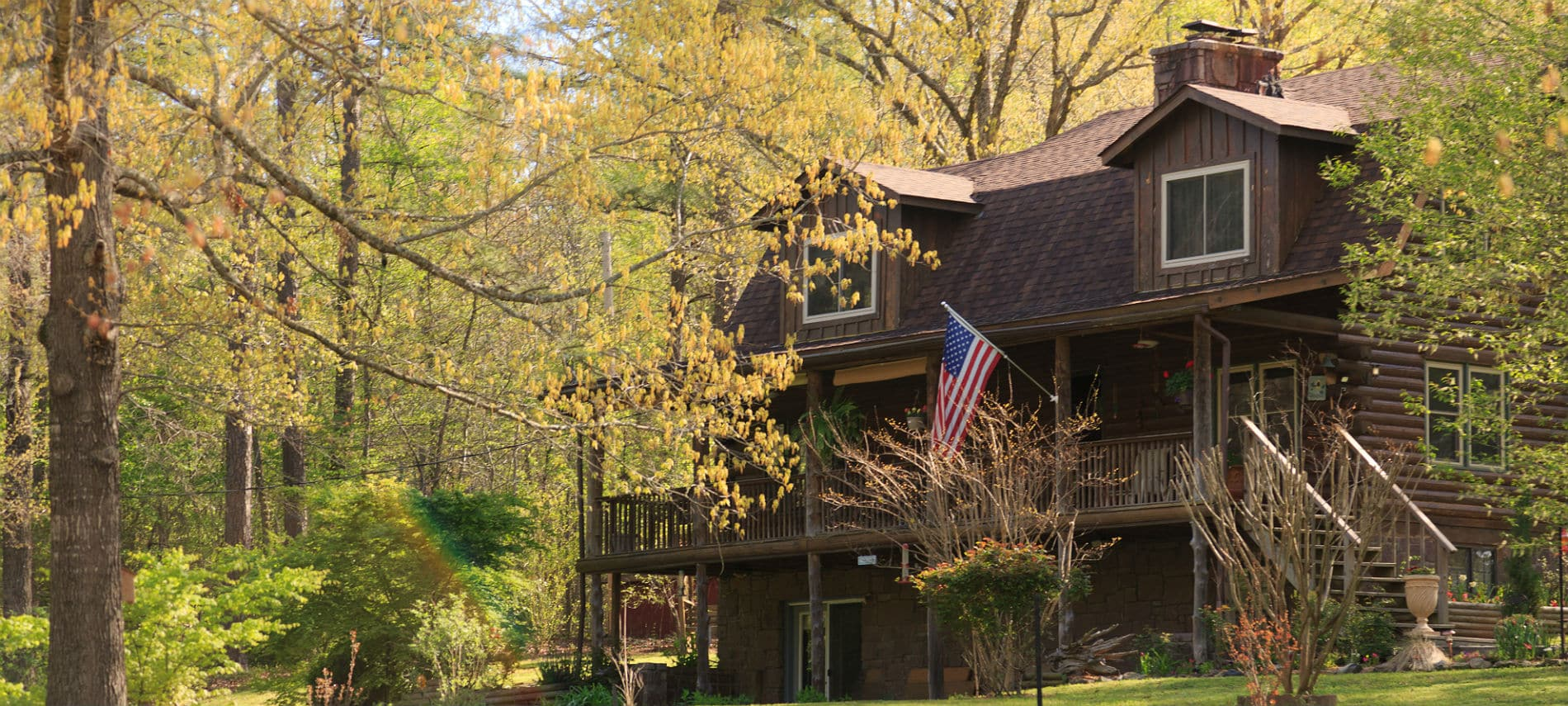 Exterior of the inn with a large front porch, log siding and an American flag hanging from the front post.