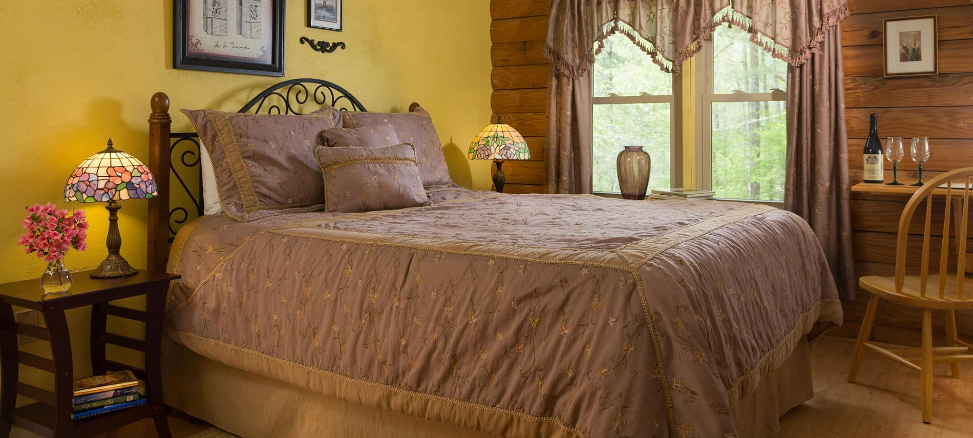 Neatly made bed with yellow and grey linens in a bedroom with yellow walls, white beadboard ceilings and tiffany lamps on the nightstands.