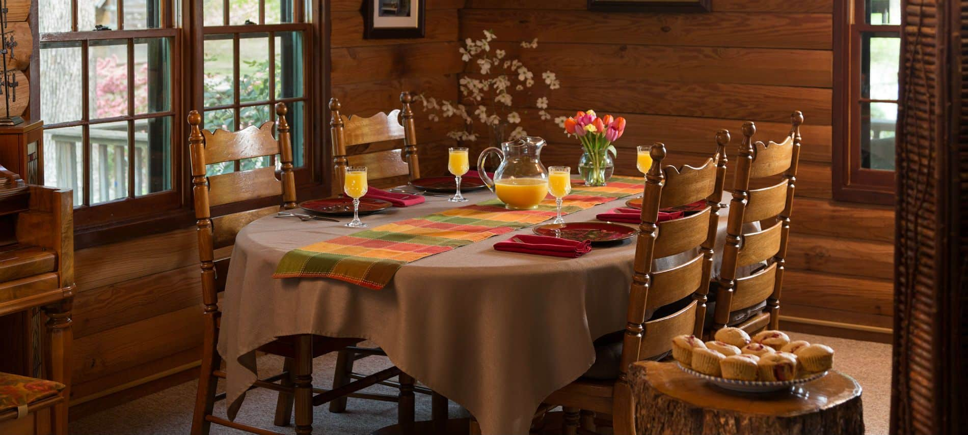 Dining room table set for four people with tan linens and multi colored napkins, orange juice and fresh flowers.