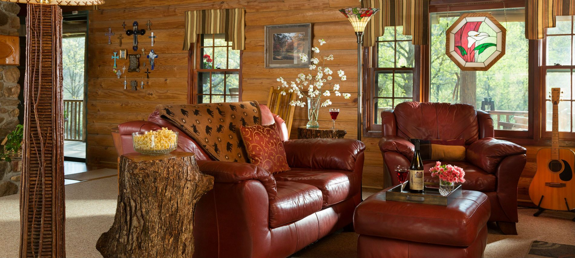 Leather sofa a side chair in a living room with log walls, rustic decor, stained glass floor lamp and window accent.