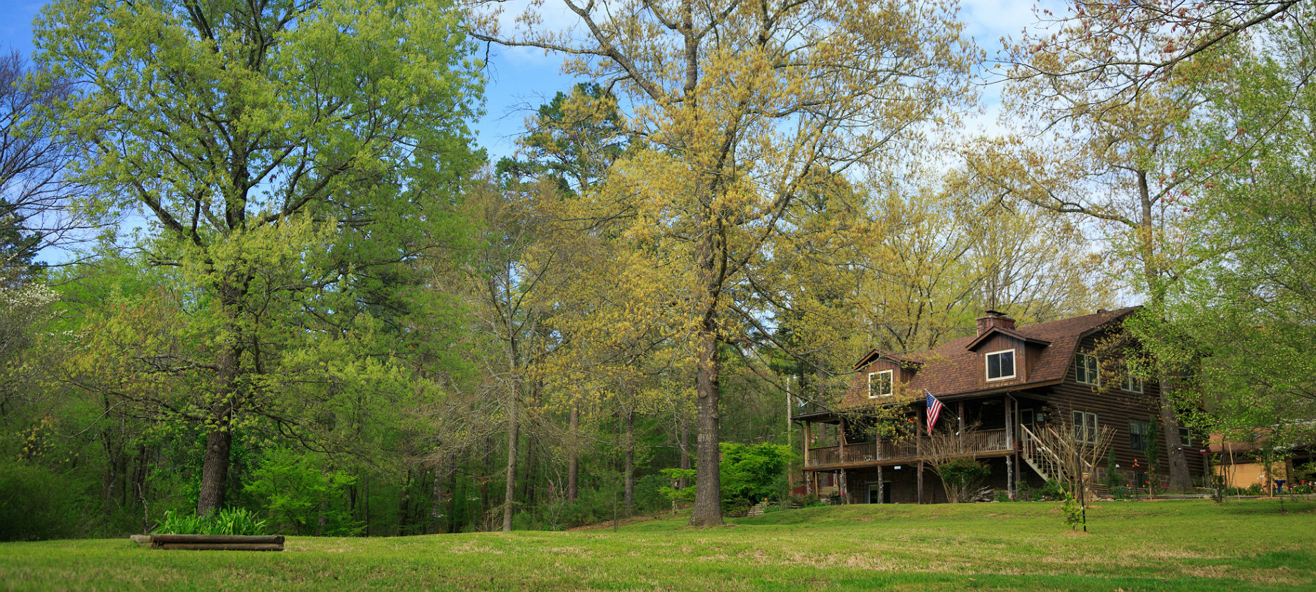 Exterior of the inn with a large outdoor porch and log construction on an expansive grassy field with a forest of mature trees surrounding.