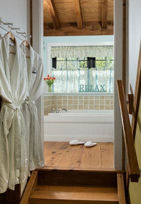 "Large soaking tub in a bathroom with a large window, hardwood floors, two white robes and a turquoise sign that reads ""Relax""."