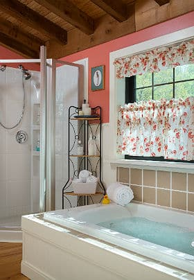Large white soaking tub with running water in a bathroom with coral colored walls, floral print valences and a corner shower.