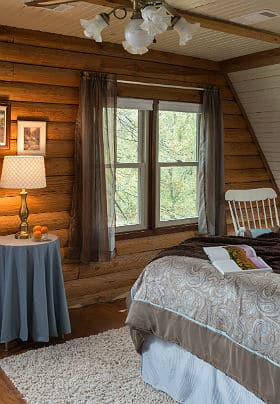 A neatly made bed facing a large picture window in a room with log walls and a white rocking chair.