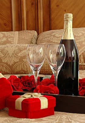 A wooden tray laying on a neatly made bed with two wine glasses, a bottle of red wine and a velvet heart shaped gift box.