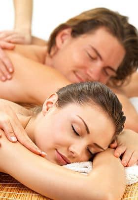 Man and woman enjoying a couples massage on bamboo mats.