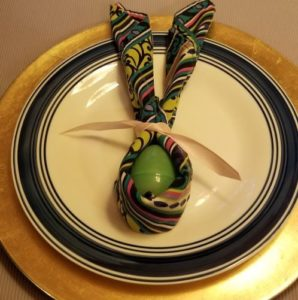 colorful napkin wrapped around a green egg and tied with a ribbon to look like bunny ears