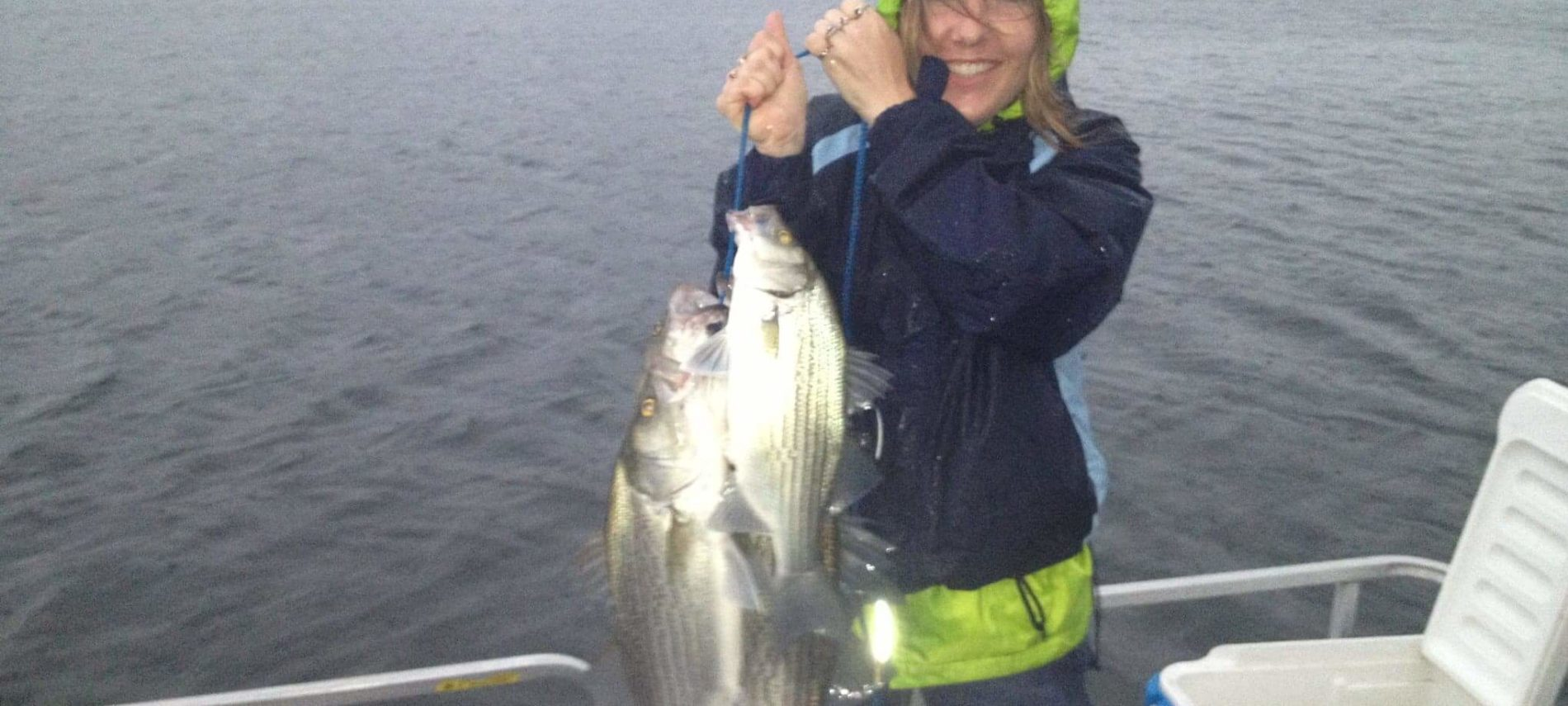 a woman holding 2 white bass while standing on a boat on a lake with trees in the background