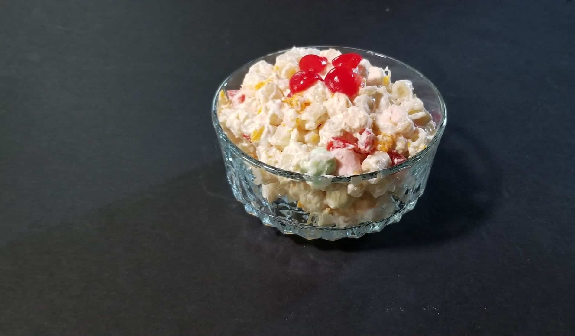 bowl of pasta salad with marshmallows and maraschino cherries on top