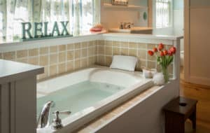 Jacuzzi tub below a window with a wooden sign that says RELAX.  A vase of orange tullips sit on the side of the tub, along with washcloths and a bath pillow.