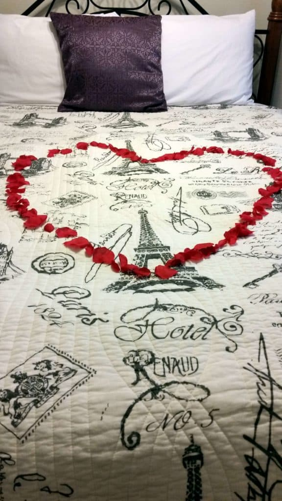 red rose petals placed on a black and white bedspread in the shape of a heart