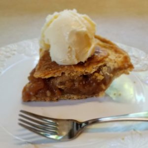 Slice of apple pie with a scoop of vanilla ice cream on top