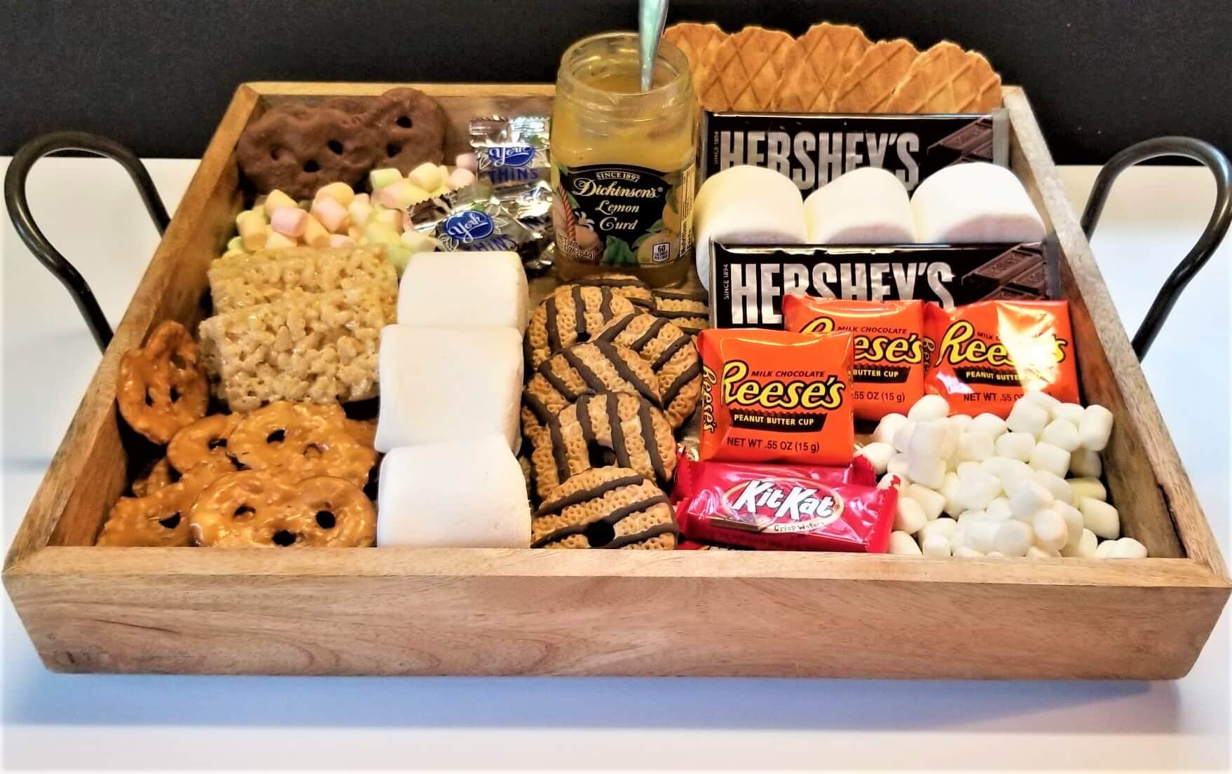a s'mores dessert tray, filled with marshmallows, chocolate candies, cookies and crackrers