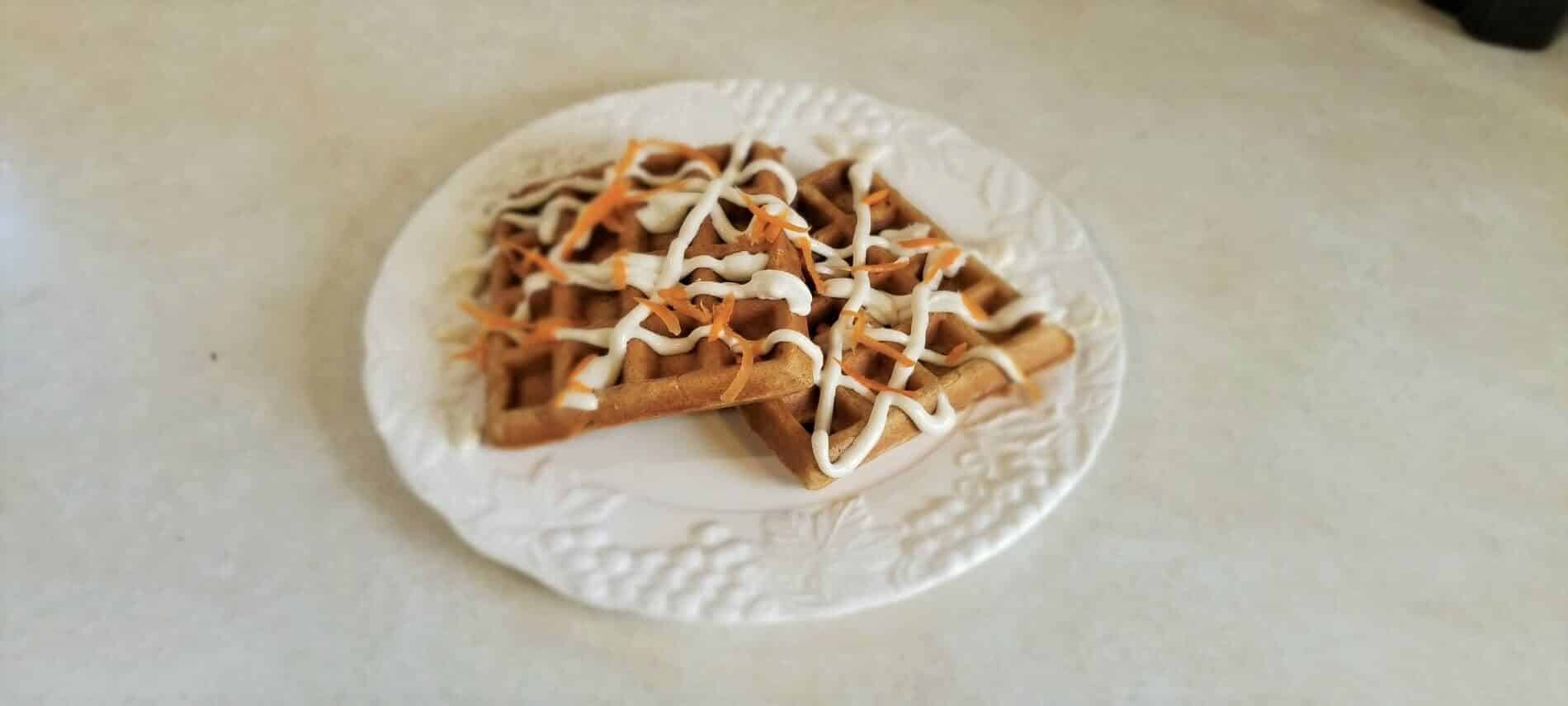 two waffles topped with cream cheese drizzle and shredded carrotson a white plate