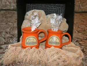 2 coffee mugs with treat bags sitting on a throw blanket